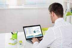 Young Businessman Analyzing Graph On Laptop In Office Stock Photos