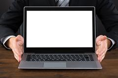 Close-up Of Businessperson Showing Blank Screen Laptop At Desk Stock Photos