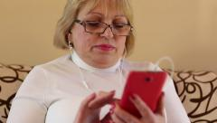 Woman with red smartphone sits on the sofa Stock Footage