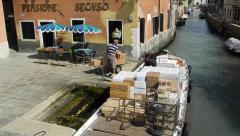 Workmen unload a cargo boat moored in a canal in Venice - stock footage