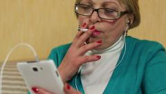 Woman in glasses with white smartphone smoking a cigarette Stock Footage