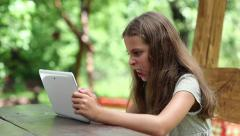 Beautiful girl with tablet computer sits on the bench in summerhouse - stock footage