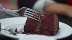4K Close up beautiful Asian woman eating chocolate cake at outdoor cafe table Stock Footage