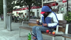Authentic emotion homeless man sitting on a bench and eats food Stock Footage