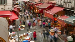 Couple stand still at crowdy street market area, people mill about, time lapse Stock Footage