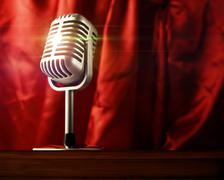 Microphone in front of stage curtains - stock photo