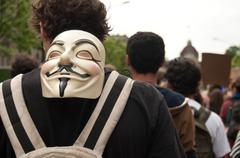 people with anonymous mask during the demonstration against Monsanto - stock photo