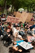 people sitting on the road during the demonstration against Monsanto - stock photo