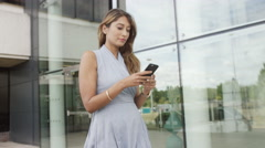 4K Attractive businesswoman looking at mobile phone as she walks outside office  - stock footage