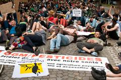 People sitting on the road during the demonstration against Monsanto Stock Photos