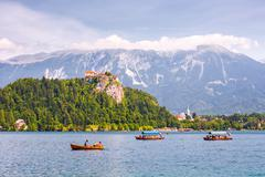 Bled Castle on a Precipice Overlooking Bled Lake with Tourists and Boats - stock photo