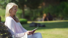 4K Portrait of beautiful mature woman using computer tablet in the park Stock Footage