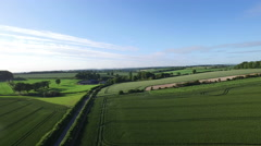 4K Aerial flight above rural road & fields in the English countryside.  Stock Footage