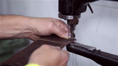 Man sewing leather in a vintage sewing machine Stock Footage