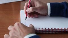 man writing in a notebook with a pen - stock footage