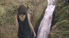 Bohemian Mixed Race Woman Walks Down Rocky Terrain To Look Out At Waterfall (4K) Stock Footage