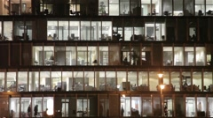 Office building with people working at night Stock Footage