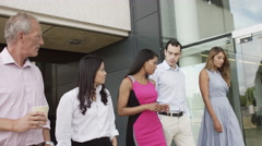 4K Attractive business team in conversation as they walk outside office building - stock footage