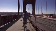 Man Rides Bike on Golden Gate Bridge   Stock Footage