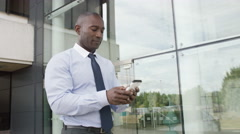 4K Attractive businessman looking at mobile phone as he walks outside office - stock footage