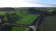 4K Aerial flight above rural road & fields in the English countryside.  - stock footage