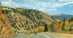 4K wide shot Motorcycles driving along mountain highway orange gold aspen trees - stock footage
