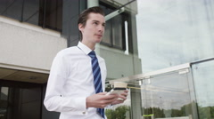 4K Young businessman looking at mobile phone as he walks outside office - stock footage