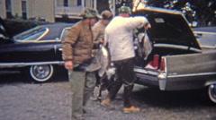 1973: Men splitting up goose hunt bounty in truck of big 70's cars. Stock Footage
