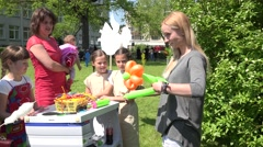 Creative girl twist flower shape from balloons for curious children. 4K Stock Footage
