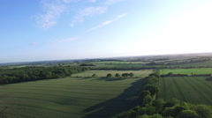 Stock Video Footage of 4K Aerial flight above forest & fields in the English countryside.