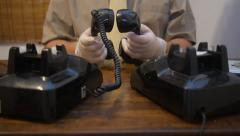 Male spy criminal kidnapper on two old telephones places hand sets together Stock Footage