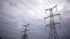 Pylons transmitting the electricity under overcast sky Stock Footage