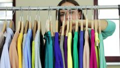 Female customer choosing clothes from rack in clothing storeHD Stock Footage