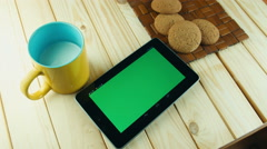 A woman uses a tablet PC at his desk. Chroma key screen for placement of your ow - stock footage