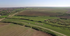 Aerial view over a plain field near a village Stock Footage