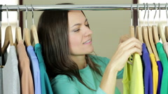Young smiling woman seller put clothing hangers at the rack HD Stock Footage
