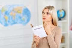 Nice girl reading dictionary Stock Photos