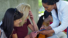 4K Attractive female friends looking at mobile phones outdoors  - stock footage