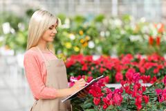 Agreeable florist holding folder Stock Photos