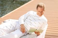 Agreeable man reading a book - stock photo
