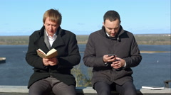 Young man on phone disturbs man withbook Stock Footage