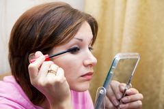 Woman tints eyes Stock Photos
