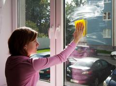 Young woman washing a window pane with yellow rag Stock Photos