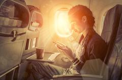 Woman sitting at airplane and looking to mobil phone. Stock Photos