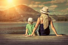 Stock Photo of Happiness mother and son on the pier at sunny day under sunlight