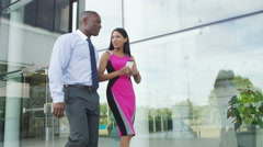 4K Attractive business man and woman in conversation as they walk outside office - stock footage