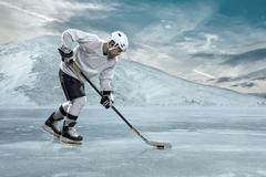 Ice hockey player on the ice in mountains Stock Photos