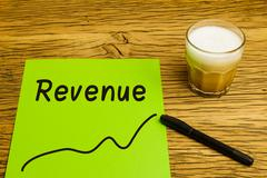 Revenue written on green paper with graph. Marker and coffee on desk. - stock photo