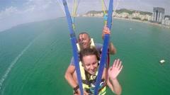 4k Flying fun couple on parachute flight Stock Footage