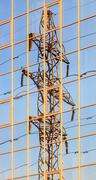 High voltage electric tower is reflected in the mirrored windows of the build Stock Photos